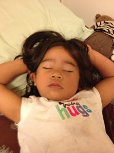 A young child sleeping due to jet lag