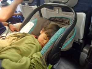 A toddler sleeping in a car seat on a plane