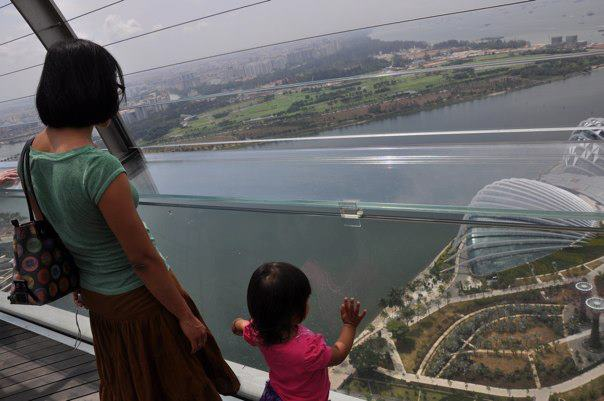 A mother and daughter, looking out at a view of Singapore, teaching girls to travel