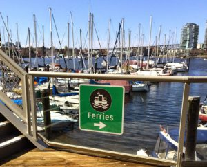 A ferry sign and sailboats docked in Vancouver, BC