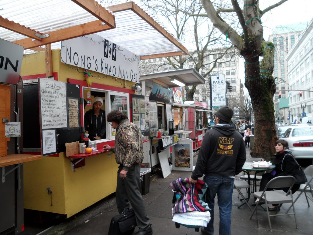 A father and his baby daughter walking by food carts in Portland, Oregon. Food is an example of costs to consider when budgeting for a road trip in the U.S.