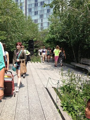 Visitors walking along the concrete sidewalk at The High Line railroad park