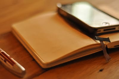 A smart phone sits on top of an open journal, ready to use apps for family activities