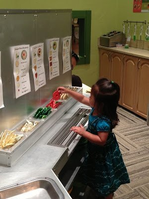 A young child playing with toy food at the Seattle Children's Museum, one of the Seattle museums for kids.