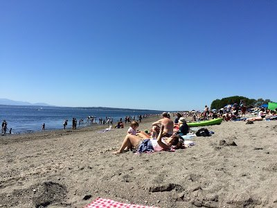 Sunbathers on the sand at Golden Gardens in Seattle, where families enjoy water activities in Seattle