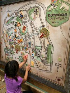 Child learning about maps in a museum, an example of why travel is educational