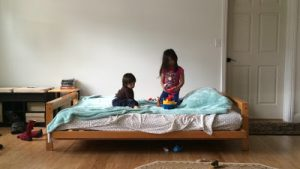 Kids playing on a bed at an Airbnb, a sharing economy travel site