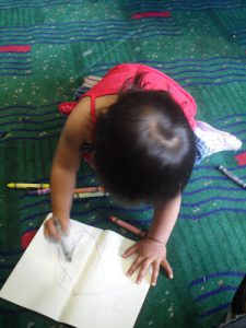 A child coloring in a book at an airport before flying with a baby