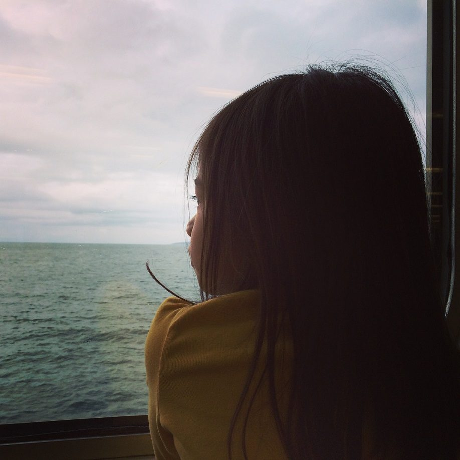 girl looking out window of boat, experiencing the educational benefits of travel