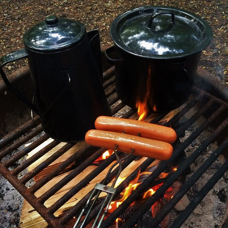 Hot dogs cooking on a campfire grill, with camping kettle and pot, during camping with a toddler
