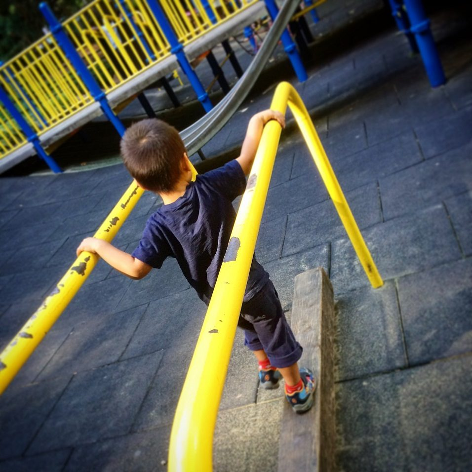 A child playing at a playground in Portland, Oregon, part of a family traveling with kids