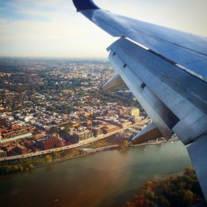 A view of airplane wings over Washington, DC to take a family around the world