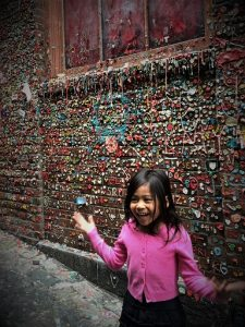 A little girl stands in front of the Gum Wall in Pike Place Market, one of the popular activities in Seattle for families to do
