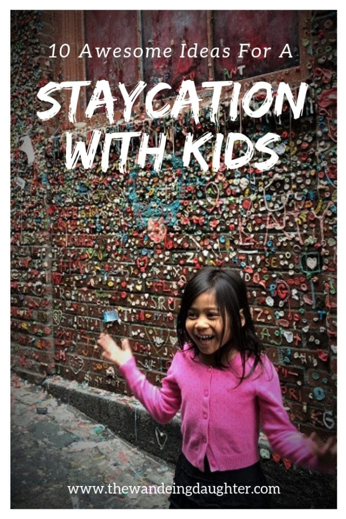 Staycation With Kids! Ten Awesome Ideas For Families   The Wandering Daughter   Creative ideas for families to spend a staycation with kids in their home town. Pinterest pin. Photo of a girl in front of a wall with wads of gum stuck to it.
