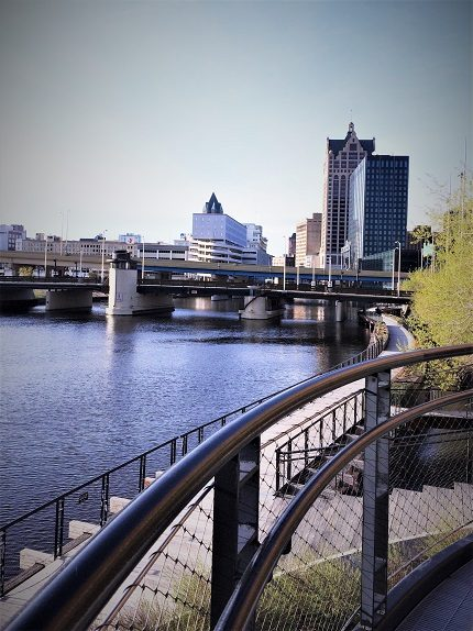 A river in Milwaukee, Wisconsin, with a sidewalk along the river. In the background are buildings in a city. The riverwalk is one of the popular Milwaukee activities for families.
