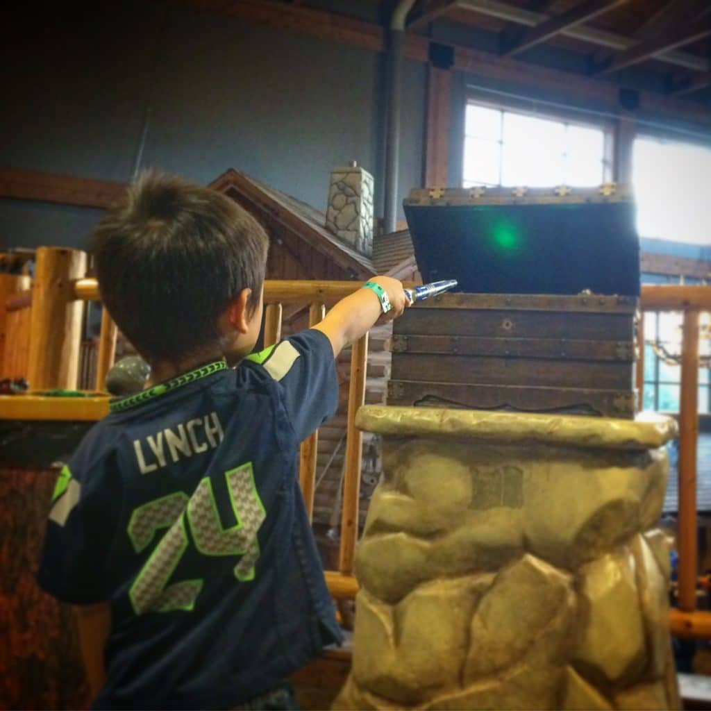 A kid at Great Wolf Lodge playing with a borrowed wand, as a way to save money at Great Wolf Lodge
