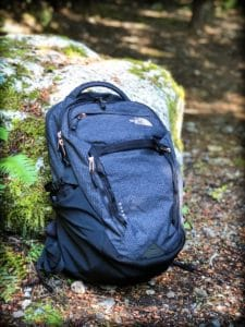 A backpack against a boulder for traveling in minimalism