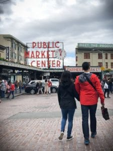 A couple walks to Pike Place Public Market in Seattle