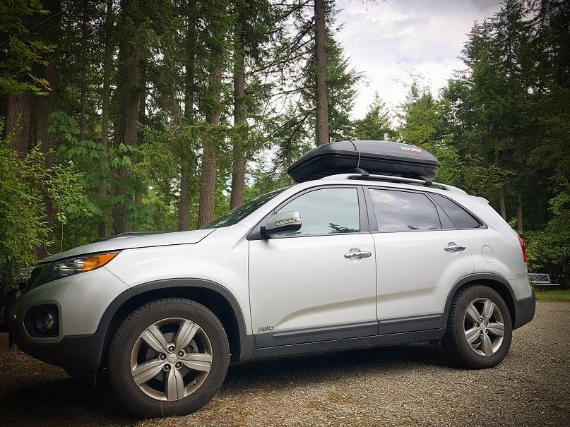 A silver SUV with a roof rack, and pine trees in the background.  The car was used for affordable world travel.