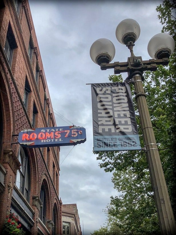 A neon sign and sign of Pioneer Square , examples of things visitors will see during a walking tour of Seattle
