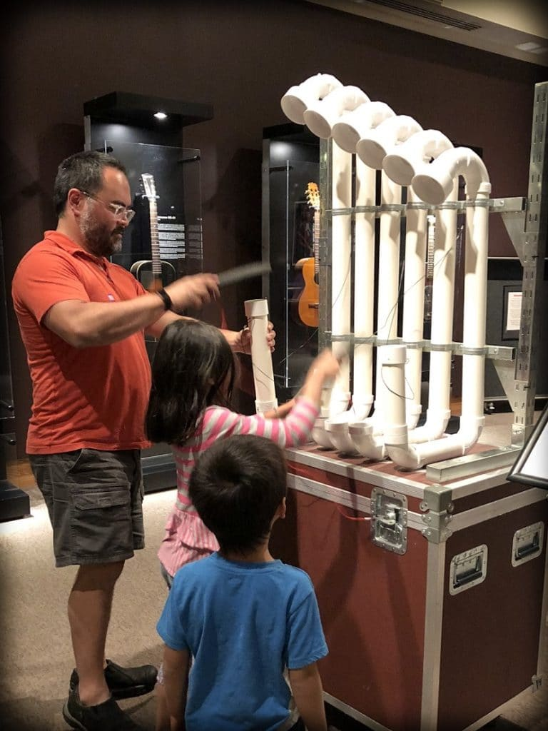 A world schooling family learning about sound and music at the Museum of the Rockies
