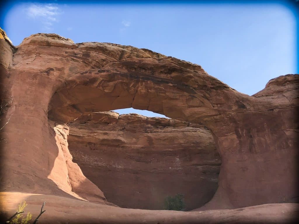 A natural arch made from red rocks at Arches National Park, one of the national parks in the West