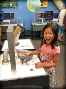 A child experiencing transformational family travel at a science museum