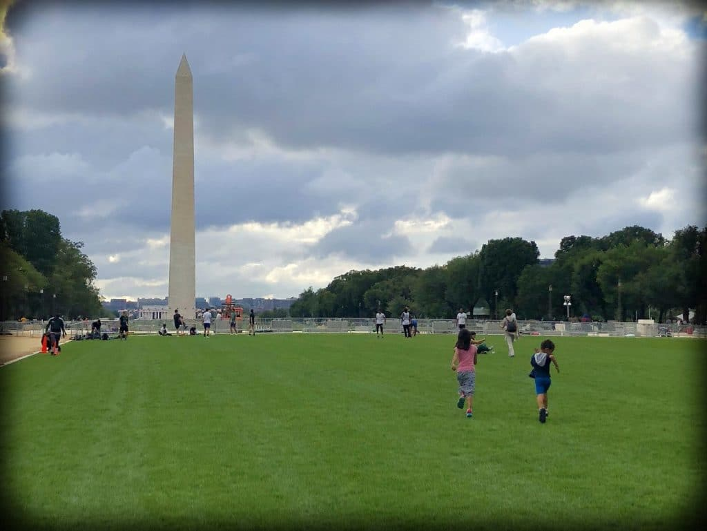 A grassy field in front of the Washington Monument at the National Mall in Washington, DC, with two kids running on the grass towards the Washington Monument, doing DC world schooling activities