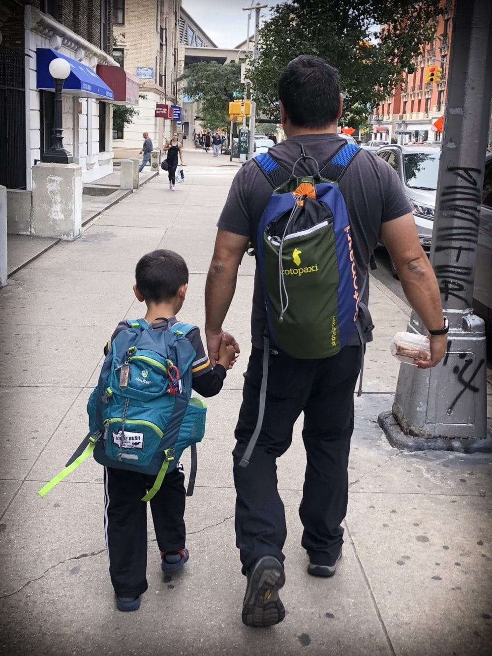 A man and son walking on a sidewalk in New York city with backpacks for minimalistic travel