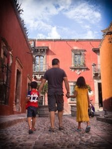 Father and kids walk on an old colonial street in Mexico