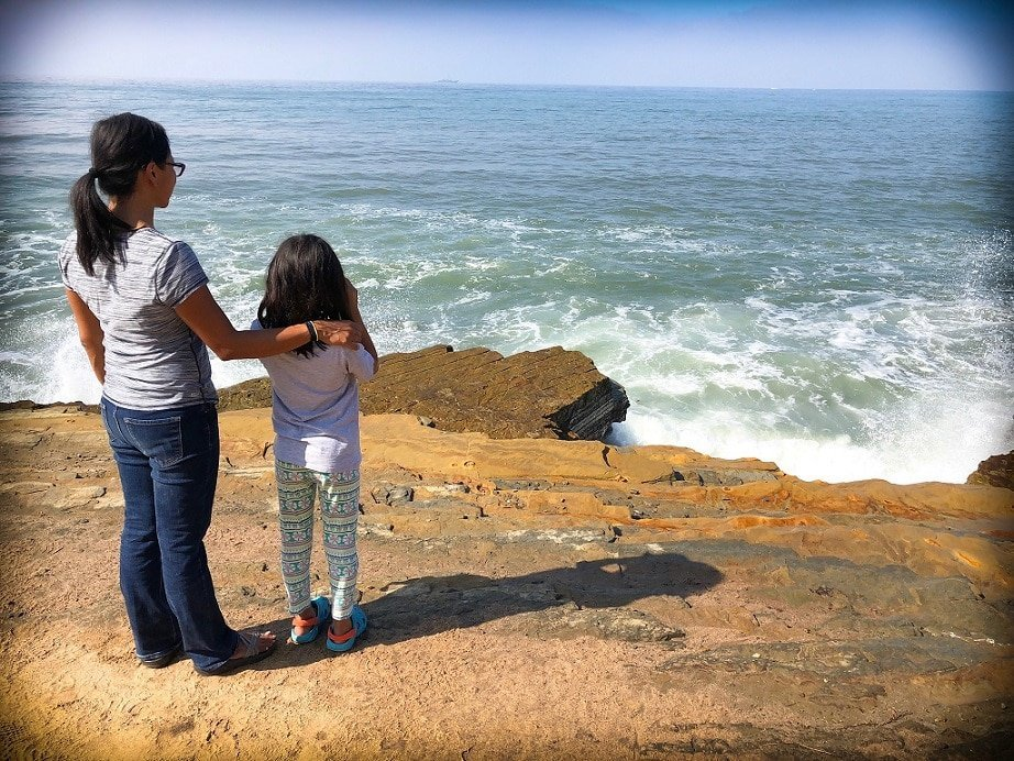 A mother and daughter standing on the edge of a cliff looking out into the ocean, teaching girls about the world