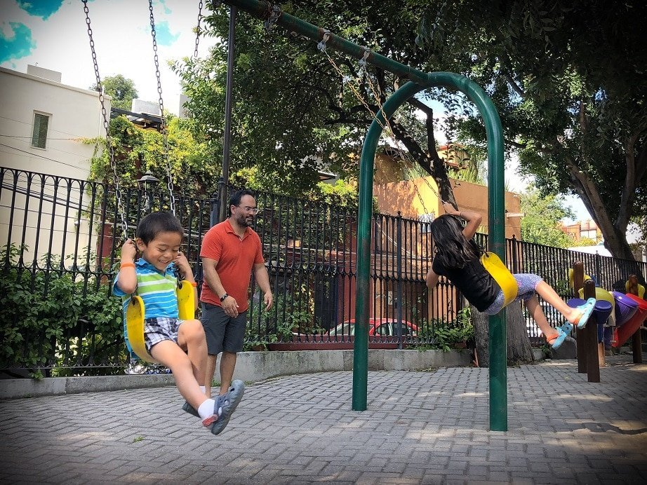 A family at a playground in San Miguel de Allende, Mexico, slow traveling