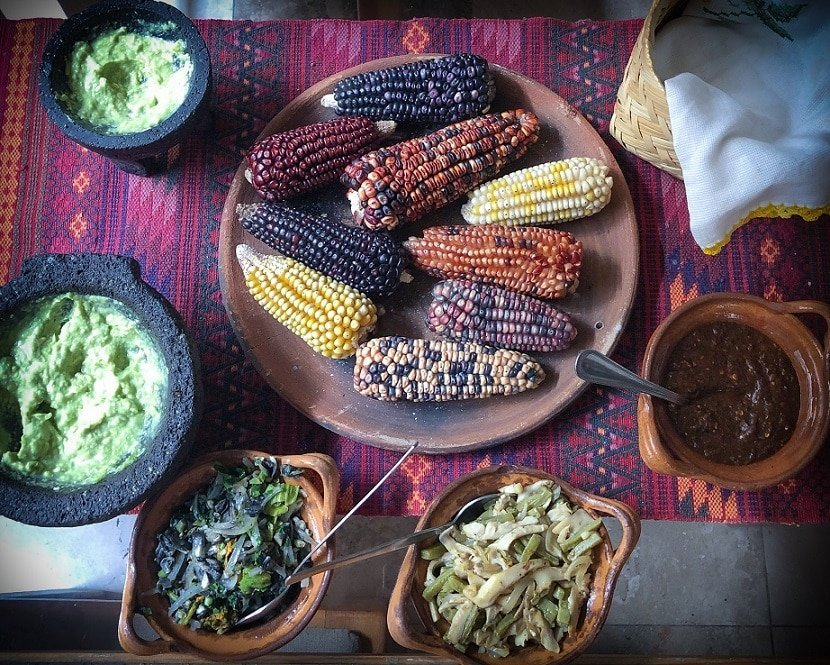 I love Mexico for its food! Dried corn on a platter, surrounded by Mexican dishes of guacamole, sauteed corn fungus, sauteed squash blossom, mole, and tortilla.