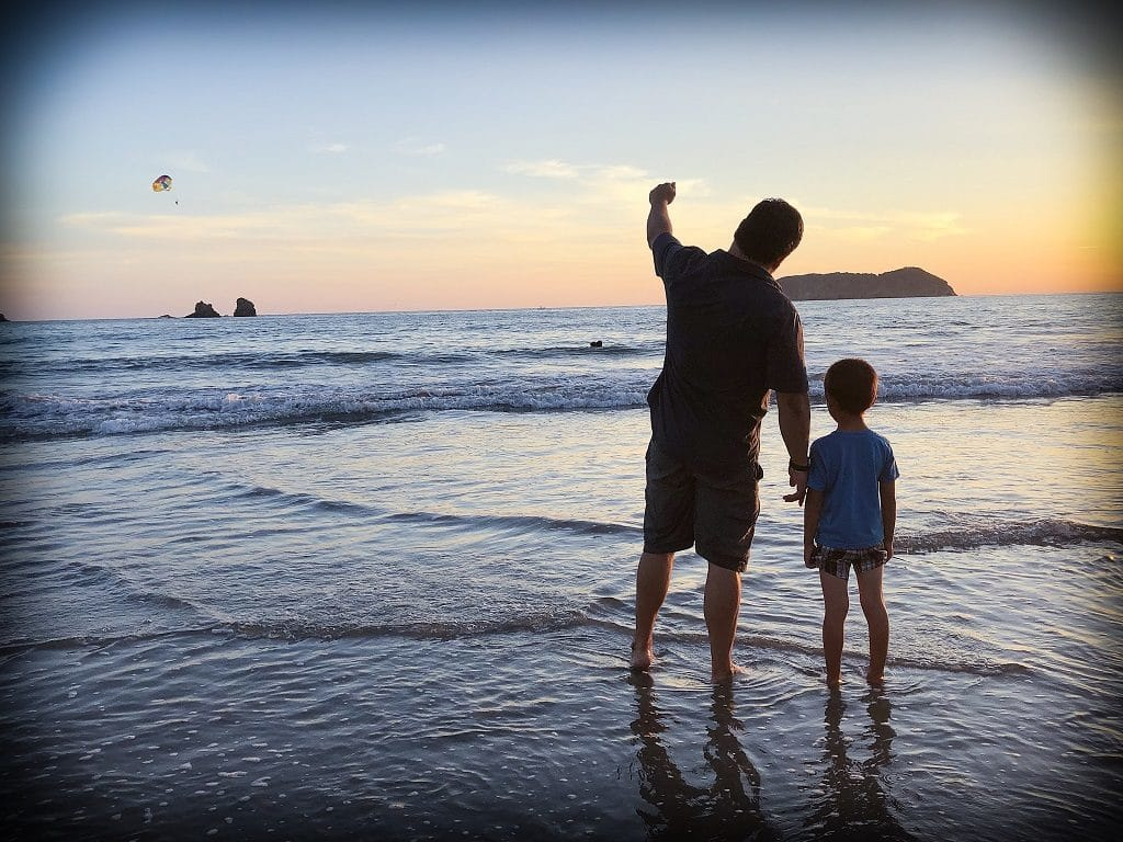 A man and a boy, examples of traveling families of color, standing on a beach looking at a sunset with water swirling at their feet