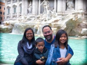 family in front of trevi fountain in rome italy