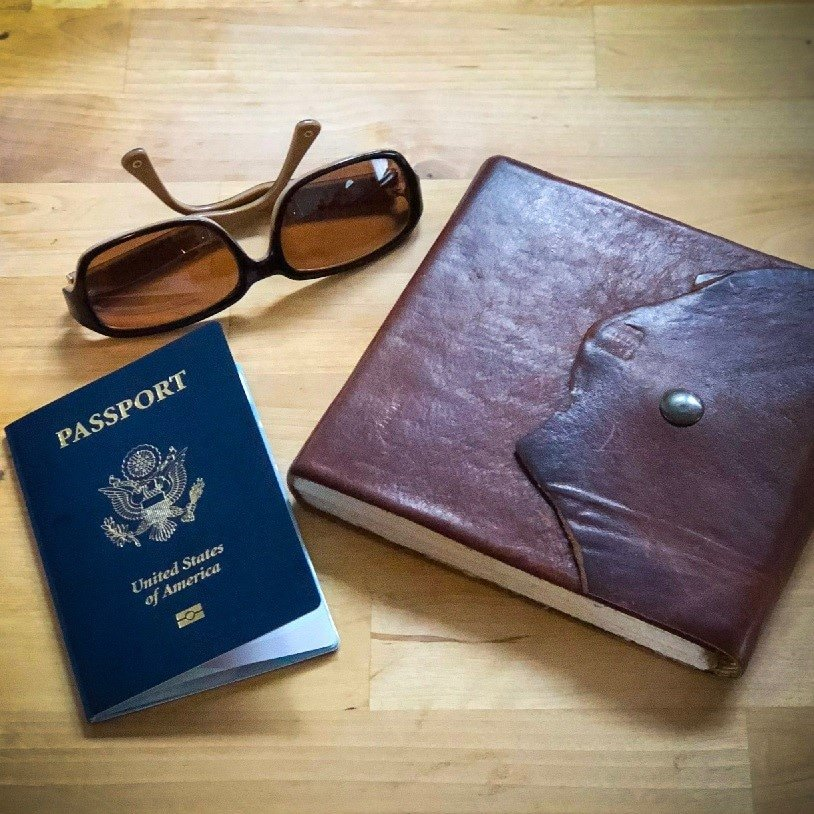 A pair of fashion sunglasses, a USA passport, and a leather-bound journal on a wooden counter.