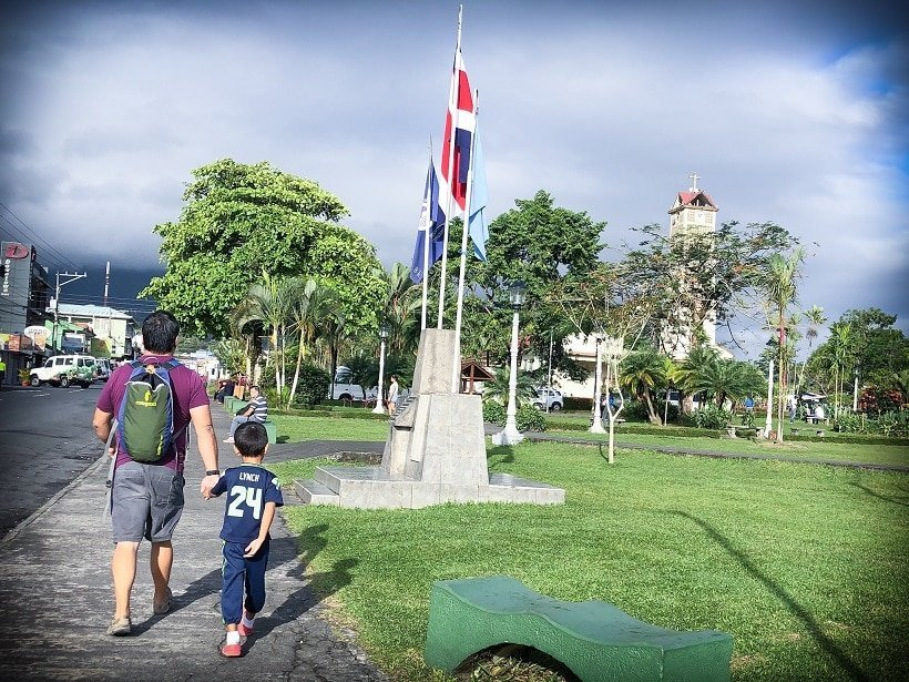 A man holding a young boy's hand, showcased on family blogs, as they walk through a small town in Costa Rica. They are passing a green field with a flag pole in the immediate distance, and a tower behind trees in the distance.