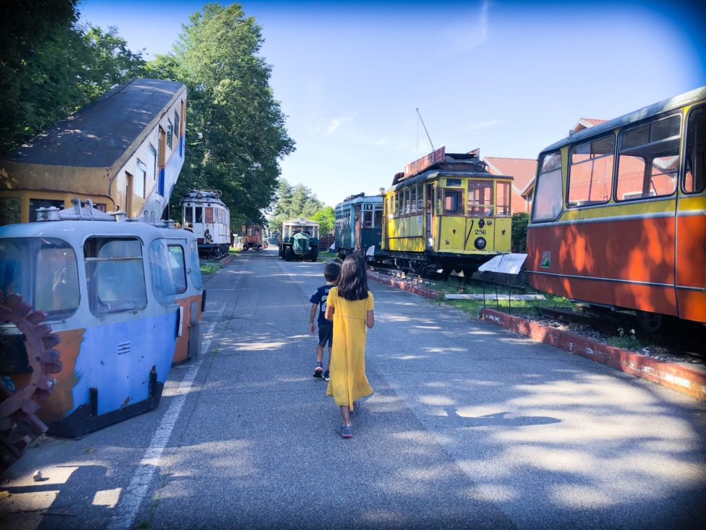 A boy in blue clothes and a girl in a yellow dress walk along a paved road at a museum of aviation in Milan, Italy. The road is lined with old trams, trolleys, and train.