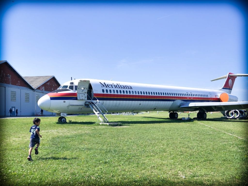 A little boy running towards an old commercial airplane at a museum of aviation in Milan, Italy.