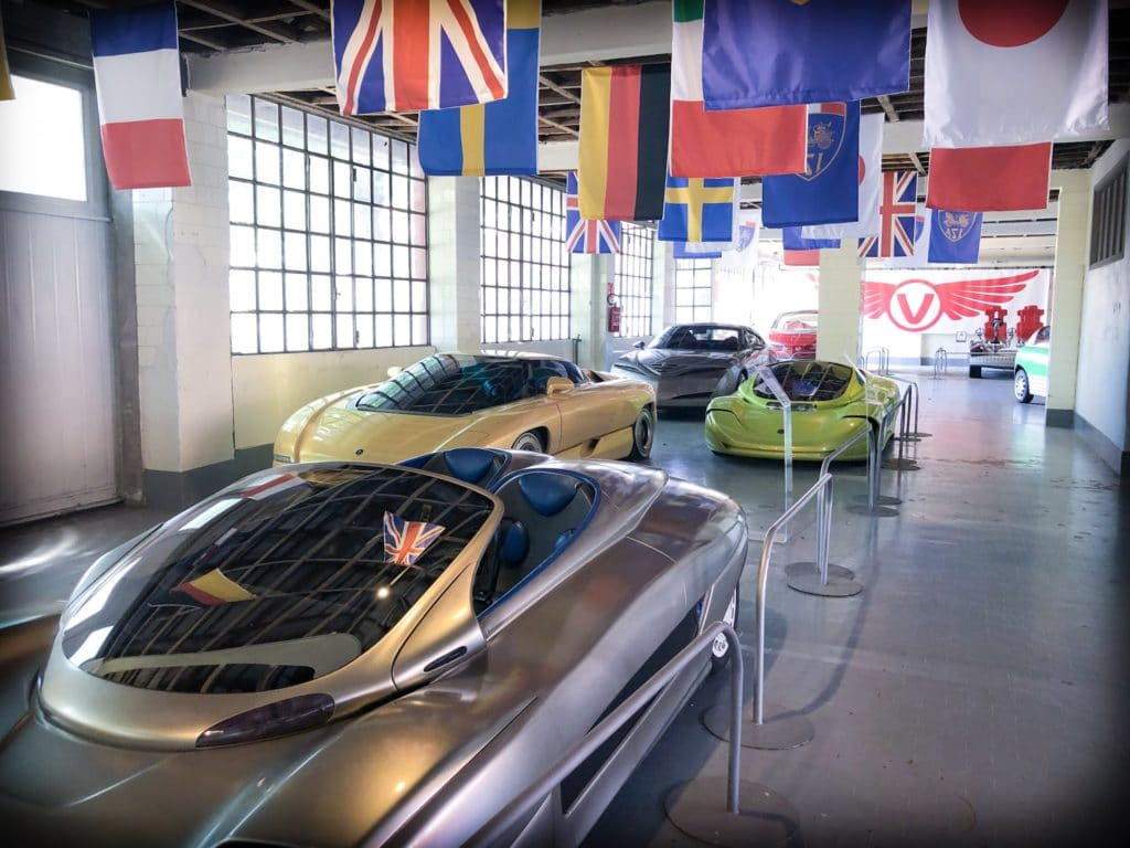 Four concept cars on display in a row at a museum of aviation in Milan, Italy. The cars are sports cars, with tinted glass.