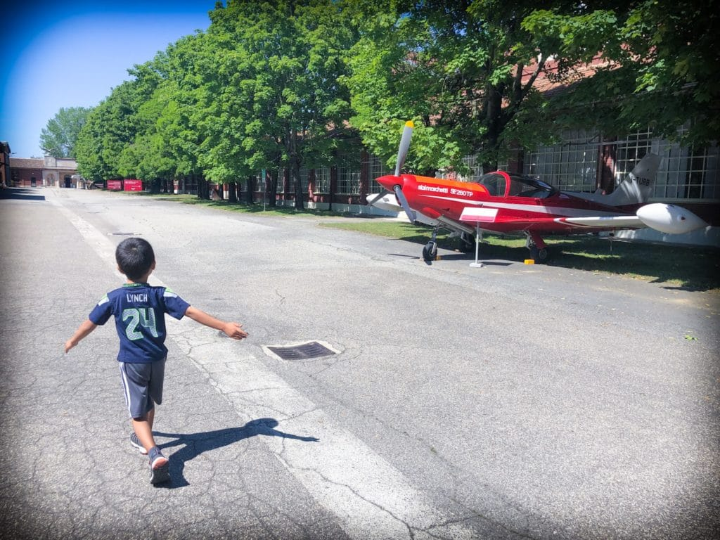 Young boy walking through the outdoor grounds of a museum of aviation in Milan, Italy, passing by a small red propeller plane.
