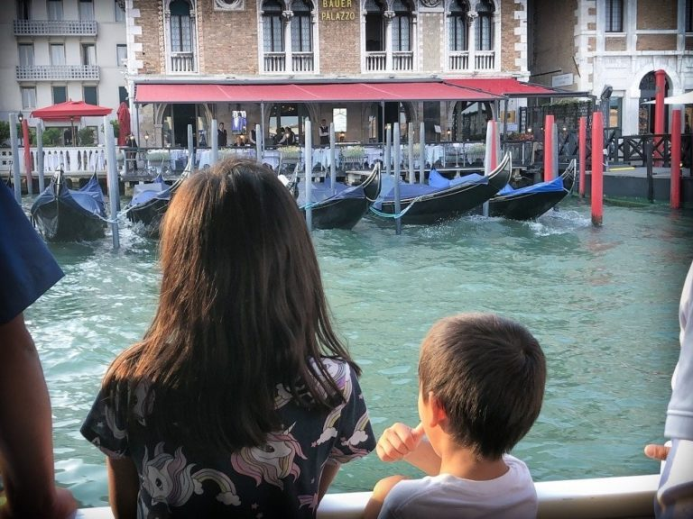 kids looking at gondolas on canal in venice italy