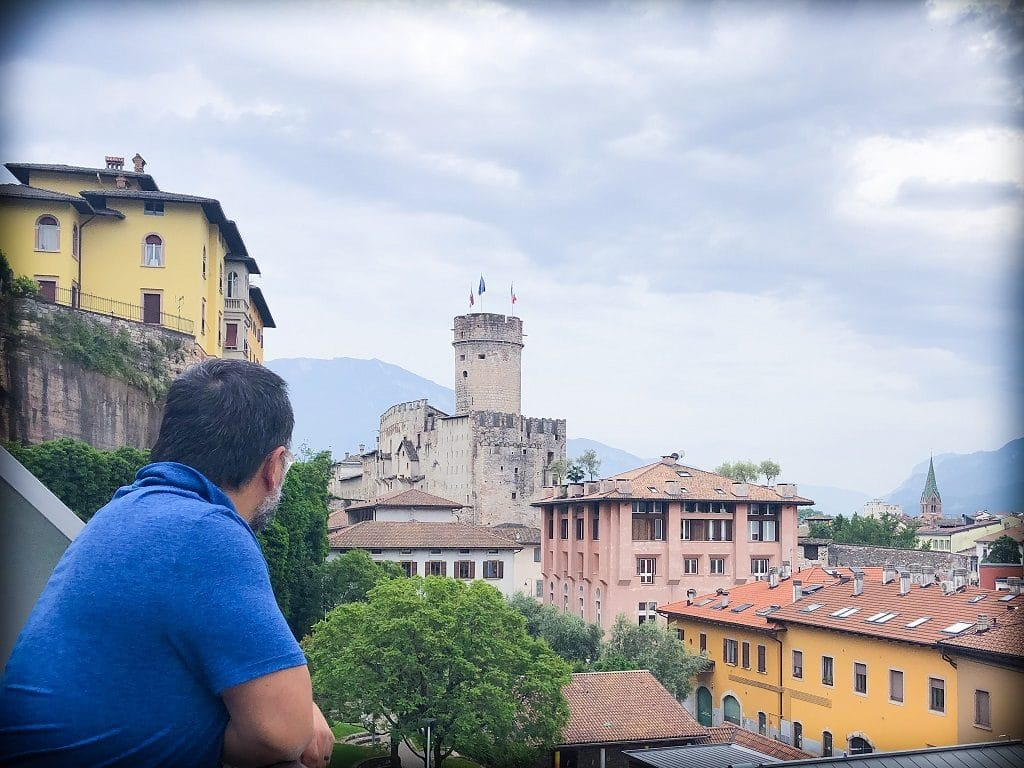 A man enjoying his Italy itinerary in Trento, Italy. He's leaning on a balcony and looking out onto a castle in the background. Surrounding the castle is a yellow building, a pink building, and an goldenrod building with a reddish-orange roof.