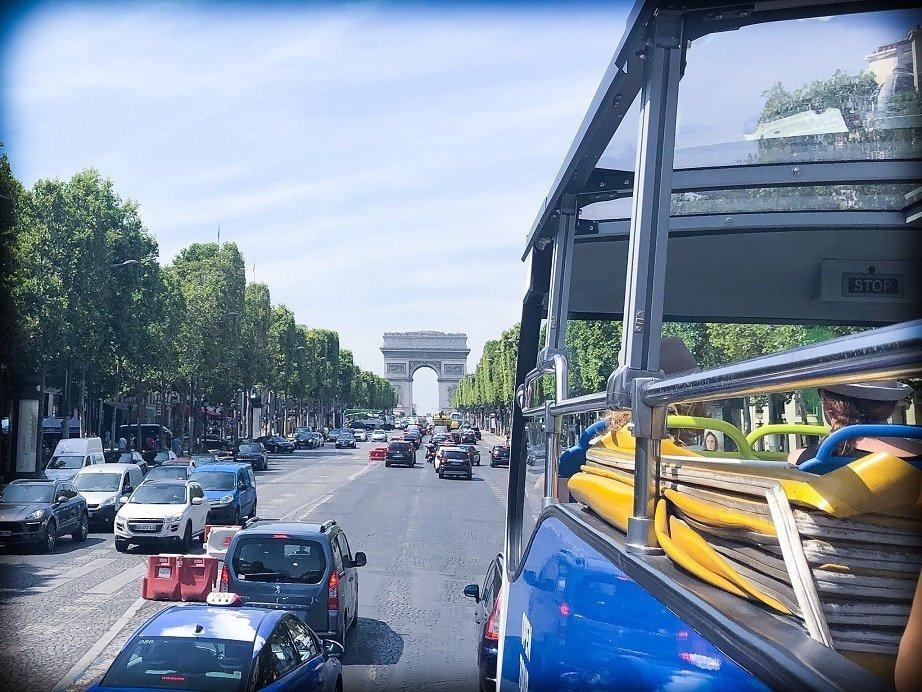 A view of Arc de Triomphe during a Paris 3 day itinerary. In the foreground corner is an open top tour bus. In the background is Arc de Triomphe, with the tree lined road filled with cars leading up to the arc.