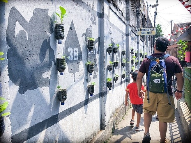 A man and boy walking past a wall with plants hanging on the wall, traveling like a local