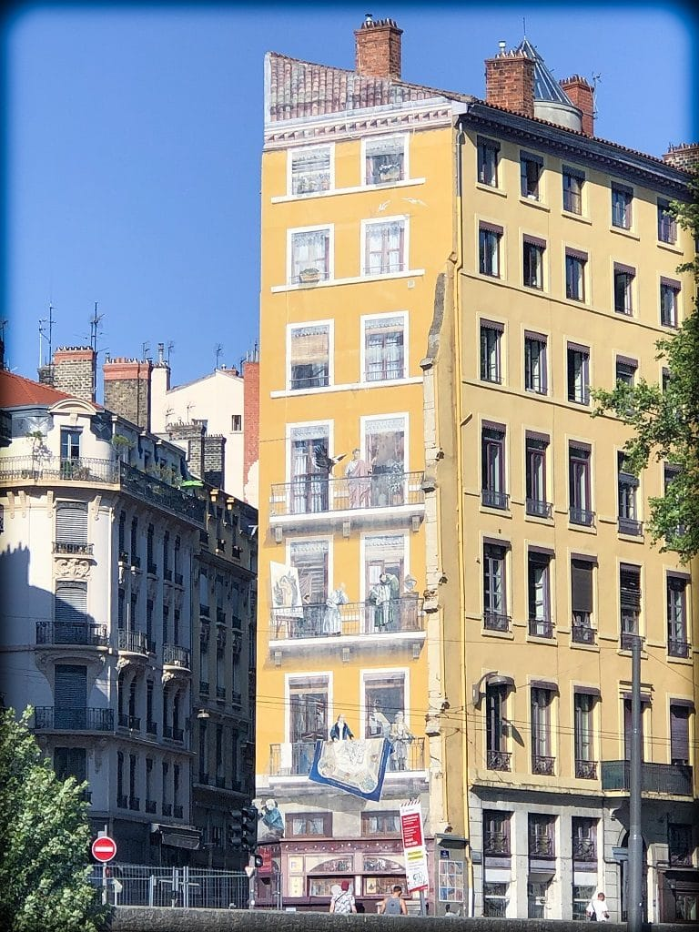 Fresco on the side of the building in Lyon, showing windows and people on balconies in front of the painted windows.