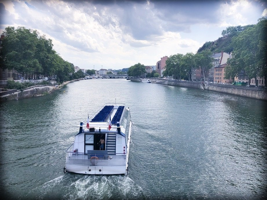 A view of the Saone River in Lyon, France, with a boat on the river in the foreground. Boat cruises are one of the things to do in Lyon.