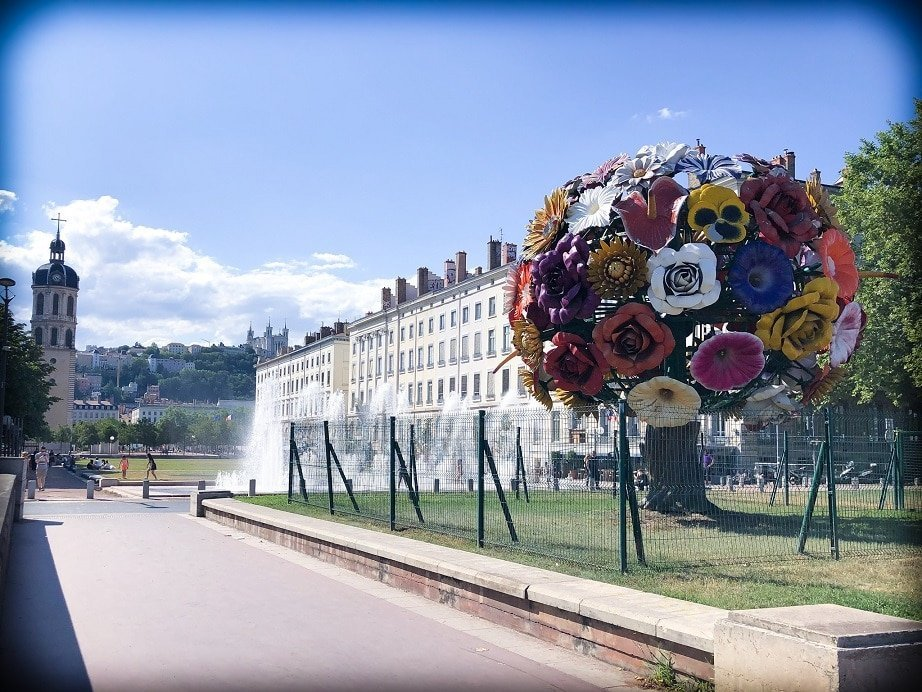 A street view of Lyon, France, with a large sculpture of a bouquet of flowers, the size of a tree on the right side of the picture.