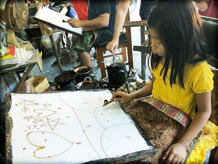 A girl doing batik art and experiencing Indonesian culture in Yogyakarta, Indonesia