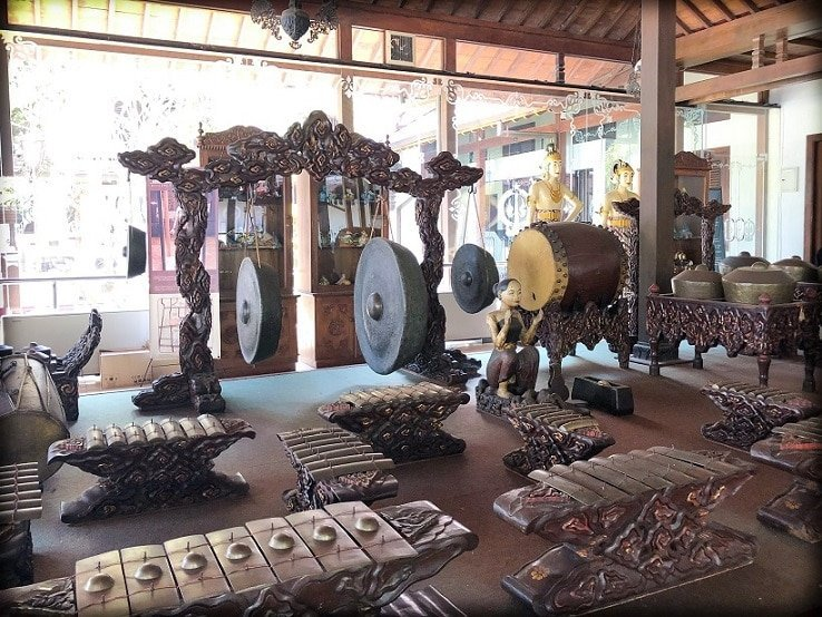 A traditional Javanese gamelan set, an example of Indonesian culture, sits on a platform, waiting to be played.
